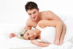 Jong paar dat op bed ligt en bij camer glimlacht Royalty-vrije Stock Fotografie