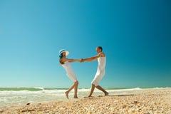 Jong paar dat op het strand tolt Stock Foto