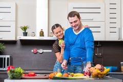Jong paar dat pret in de keuken heeft Stock Afbeeldingen