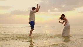 Jong paar dat pret in het overzees heeft Bestrooi water op elkaar Bij zonsondergang langzame geanimeerde video stock footage