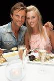 Jong paar dat in restaurant eet Stock Foto's
