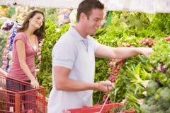 Jong paar dat in supermarktdoorgang flirt royalty-vrije stock foto