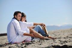 Jong paar dat van picknick op het strand geniet Royalty-vrije Stock Foto's