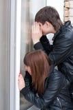 Jong paar dat in venster piept Stock Afbeeldingen