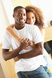 Jong Paar dat in Woonkamer omhelst Stock Fotografie