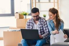 Jong paar dat zich in nieuw huis beweegt Concept huisvesting voor jonge familie Stock Afbeelding