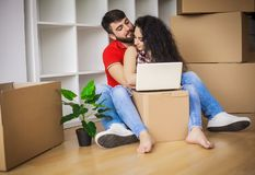 Jong paar dat zich in nieuw huis beweegt Het zitten en het ontspannen na unpac royalty-vrije stock fotografie