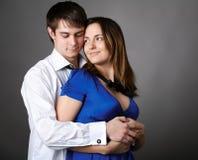 Jong paar dat zich tegen een grijze muur verenigt Stock Foto's
