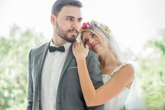 jong paar in de Bruid en de bruidegom die van het liefdehuwelijk samen en elkaar bekijken die in het park kussen omhelzen newlywe stock afbeelding