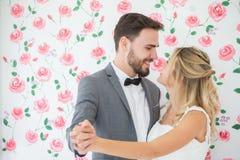 jong paar in de Bruid en de bruidegom die van het liefdehuwelijk samen en elkaar op rozenachtergrond dansen bekijken newlyweds Po stock afbeeldingen