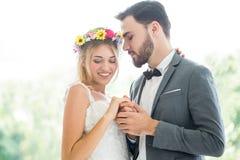 jong paar in de Bruid en de bruidegomholdingshand van het liefdehuwelijk samen en bekijkend elkaar die in het park kussen newlywe royalty-vrije stock foto's