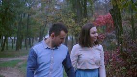 Jong paar in de handen van de liefdeholding en het lopen door een park op een de herfstdag stock footage