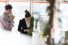 Jong paar die aan tikraad op kantoor werken Stock Afbeelding