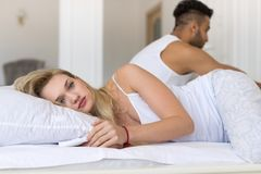 Jong Paar die in Bed liggen, die Conflictprobleem, de Droevige Negatieve Emoties Spaanse Mens en Vrouw hebben stock foto