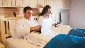 Jong paar die in bed liggen en aan laptop en tabletcomputer werken Royalty-vrije Stock Fotografie
