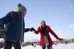 Jong paar die bij ijsbaan schaatsen, die handen houden Stock Afbeelding