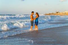 Jong paar die blootvoets op een nat strand lopen bij Stock Foto