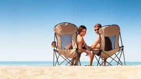 Jong paar die in comfortabele chears op het wilde overzeese strand situeren en sm Royalty-vrije Stock Afbeeldingen