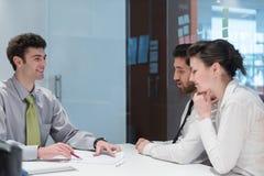 Jong paar die contractdocumenten op partners terug ondertekenen Stock Fotografie