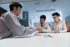 Jong paar die contractdocumenten op partners terug ondertekenen Stock Foto's
