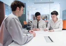 Jong paar die contractdocumenten op partners terug ondertekenen Stock Afbeeldingen