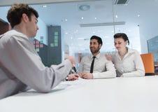 Jong paar die contractdocumenten op partners terug ondertekenen Stock Afbeelding