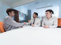 Jong paar die contractdocumenten op partners terug ondertekenen Royalty-vrije Stock Foto