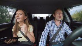 Jong paar die in de auto gaan, en de tablet glimlachen gebruiken dansen 4K stock videobeelden