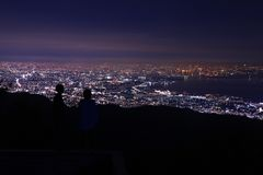 Jong paar die de lichten van de nachtstad vanaf de bovenkant van berg bekijken royalty-vrije stock afbeelding