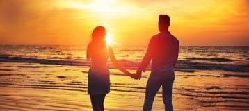Jong paar die de romantische, tropische zonsondergang bekijken stock afbeelding