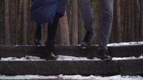 Jong paar die de treden in de winterpark reduceren Clouse-op van de voeten van het paar stock footage