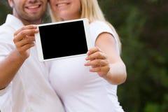 Jong paar die digitale tablet tonen bij camera Stock Fotografie
