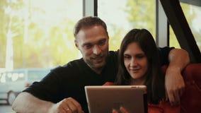 Jong paar die digitale tabletcomputer met behulp van Koffie stock video