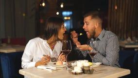 Jong paar die diner in een restaurant hebben Een jonge mens voedt zijn meisje met kaastaart en lacht stock footage