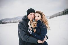 Jong paar die een gang met hun hond in sneeuwplatteland hebben Stock Foto