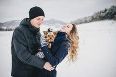 Jong paar die een gang met hun hond in sneeuwplatteland hebben Stock Afbeeldingen