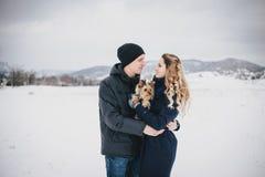 Jong paar die een gang met hun hond in sneeuwplatteland hebben Royalty-vrije Stock Foto's