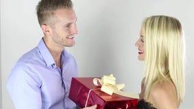 Jong paar die een gift op een witte achtergrond geven stock footage