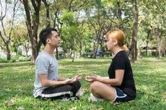 Jong paar die een meditatie maken om hun mening te kalmeren na het uitoefenen in park met een warme lichte zonneschijn in middag Royalty-vrije Stock Foto
