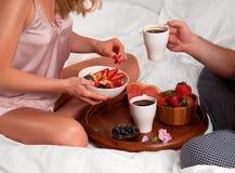 Jong paar die een ontbijt in het bed hebben stock afbeeldingen