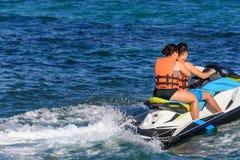 Jong paar die een straalski in Caraïbische overzees berijden, die veiligheidsjasjes dragen Riviera Maya, Mexico stock fotografie