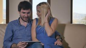 Jong paar die een tablet op de bank gebruiken stock videobeelden