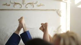 Jong paar die en in bed thuis in slaapkamer kussen knuffelen stock video