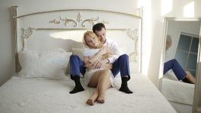 Jong paar die en in bed thuis in slaapkamer kussen knuffelen stock videobeelden