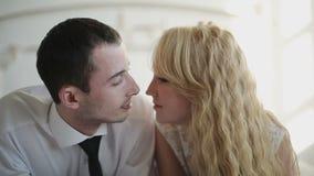 Jong paar die en in bed thuis in slaapkamer kussen knuffelen Langzame Motie stock video
