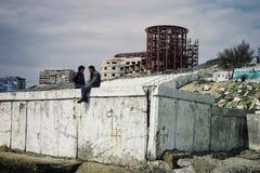 Jong paar die en op de strandboulevard van de woestijn ex sovjetstad babbelen spreken royalty-vrije stock afbeelding
