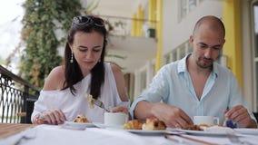 Jong paar die en tijdens ontbijt door lijst in de openluchtkoffie eten spreken stock video