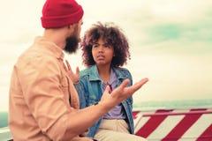 Jong paar die gebaren gebruiken terwijl het hebben van ernstige bespreking stock foto