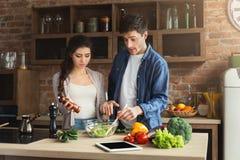 Jong paar die gezond voedsel samen koken royalty-vrije stock afbeeldingen