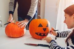 Jong paar die hefboom-o-lantaarn maken voor Halloween op keuken Tekening en scherpe pompoen royalty-vrije stock fotografie